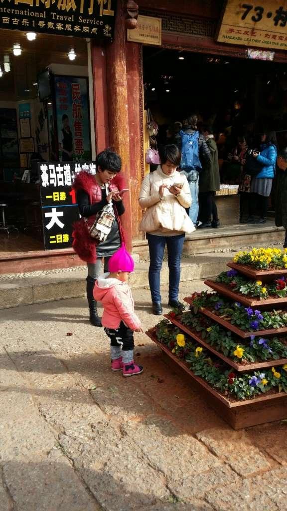 Madres chinas con teléfono móvil y niño